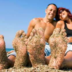 man and woman with their feet in the ocean sand