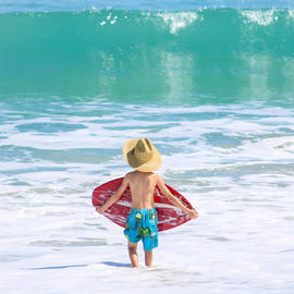 little boy boogie boarding in the ocean