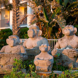 four monkey statues holding sea shells