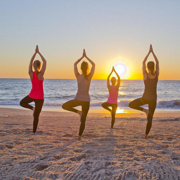 four women doing yoga on the beach at costa d'este