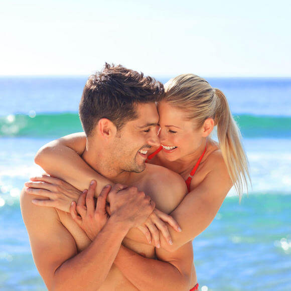woman and man embracing on the beach at costa d'este