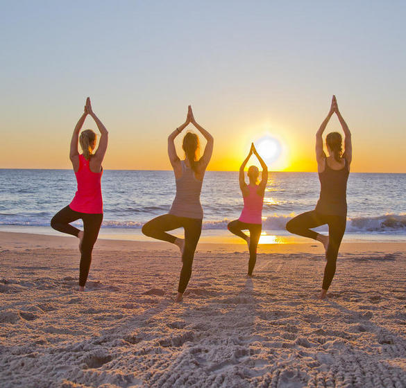 Women on the beach practicing yoga