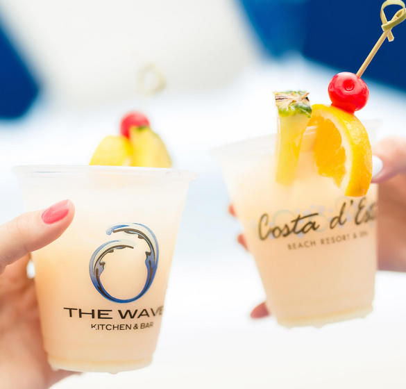 Two people holding alcoholic drinks in Coste d' Este and The Wave Kitchen branded cups